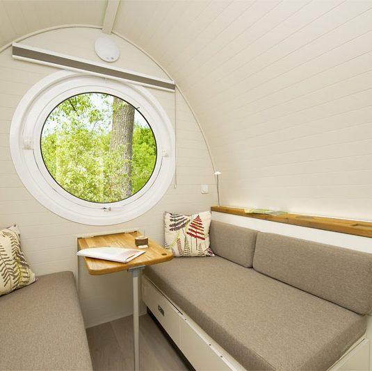 Vue intérieure d'une maison glamping, canapé et lit